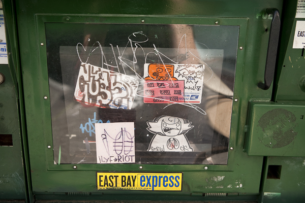 stickers on newspaper racks, oakland sticker art